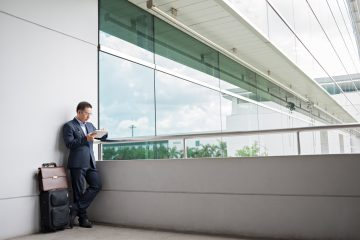 Businessman using digital tablet while waiting for the departure at the airport