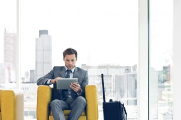 Businessman sitting in a chair and waiting for a meeting or plane, using a digital tablet.